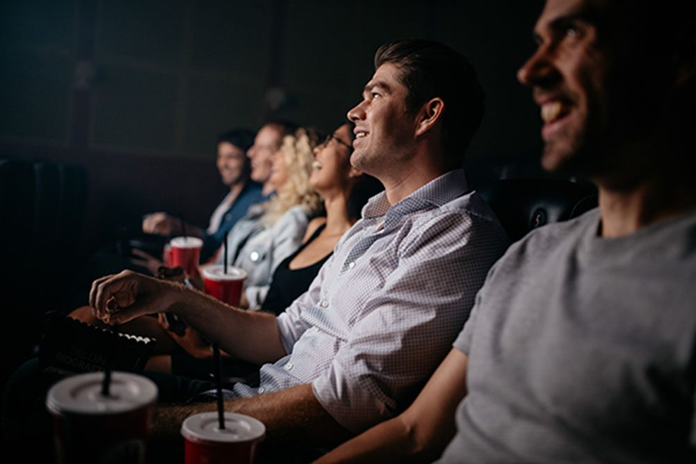 Group of young people sitting in cinema hall watching movie. Multiracial group of friends watching movie in theater.