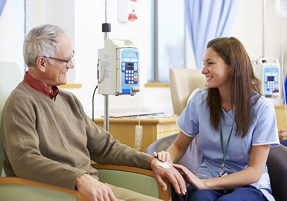 Senior Man Undergoing Chemotherapy With Nurse